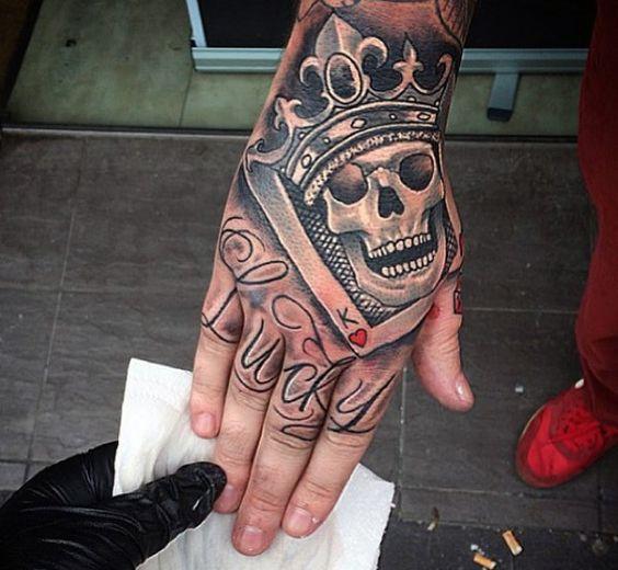 Tatuagem coroa e caveira na mão
